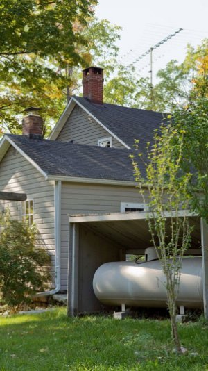 A view of a two-story house from outside. A 1,000 gallon propane tank sits under an enclosure about 15 feet from the house.