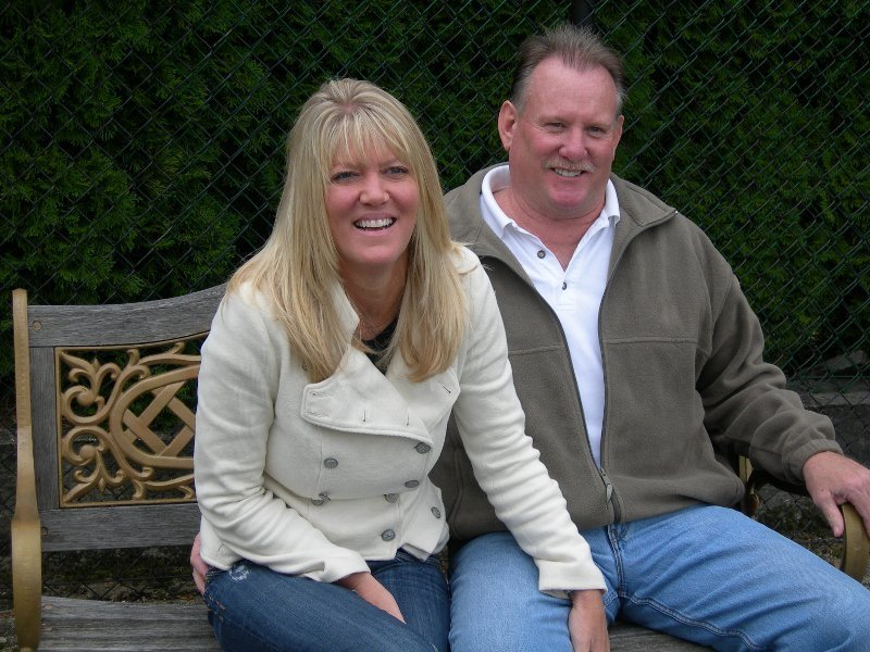 John and his wife sit next to each other, grinning. John has a grey moustache and his wife has long blonde hair.