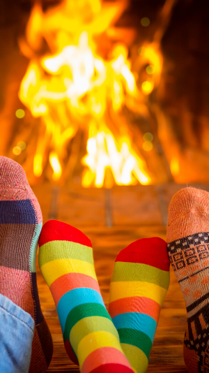 Two people warm their colorful socks by the fire
